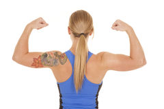 Fitness woman blue tank back flex close. A woman looking forward flexing her muscles showing off her toned arms a d flower tatoo royalty free stock images