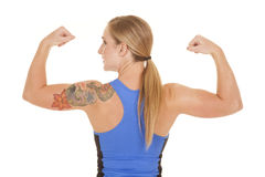 Fitness woman blue tank back flex look side. A woman looking over her shoulder while she flexes her muscles stock images