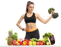 Fitness woman with a broccoli dumbbell behind a table with fruit. And vegetables isolated on white background Stock Photo