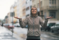 Fitness woman catching rain drops in the city Royalty Free Stock Photo