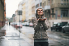 Fitness woman catching rain drops in the city. Happy fitness young woman catching rain drops in the city Stock Images