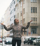 Fitness woman catching rain drops in the city. Portrait of happy fitness young woman catching rain drops in the city Stock Images