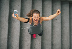 Fitness woman with cell phone outdoors in the city. Portrait of happy fitness young woman with cell phone outdoors in the city rejoicing Royalty Free Stock Photo
