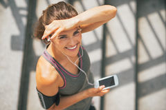Fitness woman with cell phone outdoors in city Royalty Free Stock Image