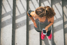 Fitness woman with cell phone outdoors in city Royalty Free Stock Photography