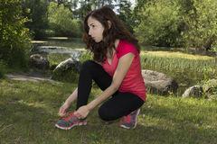 Fitness woman concentrated before sports tying her sports shoes Stock Image