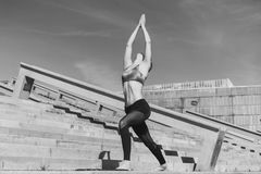 Fitness woman concept. Yoga and meditation in a modern urbanistic city. Young attractive girl - yoga meditates against. Modern skyscrapers. Black and white stock photos