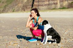 Fitness woman and dog on beach. Relaxed fitness woman with dog listening music with sport arm band and earphones at the beach. Sporty girl taking a breath before Stock Photography