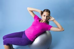Fitness Woman doing an abdominal exercise. A beautiful hispanic woman working out on an medicine ball doing crunches Royalty Free Stock Images