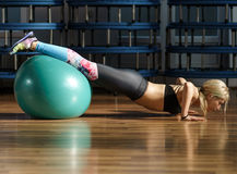 Fitness woman doing abs workout with a ball. Sporty female in a fitness gym doing abs workout with a ball Stock Photo