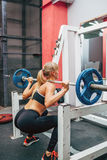 Fitness woman doing barbell squats in a gym Stock Images