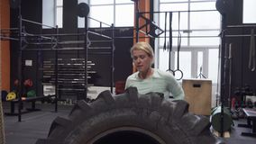 Fitness woman doing big tire flips exercise during functional training stock video