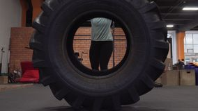 Fitness woman doing tire flips workout at gym stock video footage