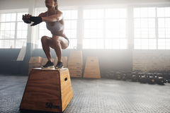 Fitness woman doing box jump workout at crossfit gym. Shot of a young woman jumping onto a box as part of exercise routine. Fitness woman doing box jump workout