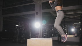 Fitness woman doing box jump workout at gym. Shot of a young woman jumping onto a box as part of exercise routine stock footage