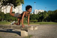 Fitness Woman Doing Buttock Exercise. Young Fitness Woman Doing Buttock Exercise in the City Park on the Concrete Bench royalty free stock images