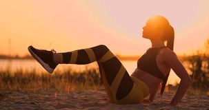 Fitness woman doing crunches at the beach. Fitness woman doing crunches exercise workout towards the beach. Female fit stock video footage
