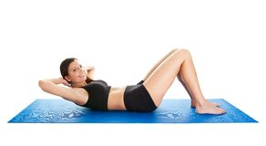 Fitness woman doing crunches on gym mat Stock Images