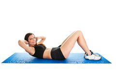 Fitness woman doing crunches on gym mat stock image