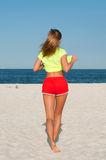 Fitness woman doing exercise on the beach. Stock Photography