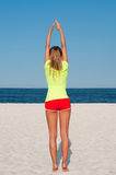 Fitness woman doing exercise on the beach. Royalty Free Stock Photo