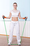 Fitness woman doing exercise with expander Royalty Free Stock Images
