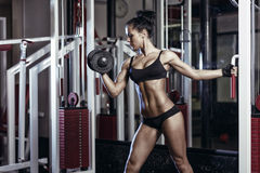 Fitness woman doing exercises with dumbbell in the gym Royalty Free Stock Images