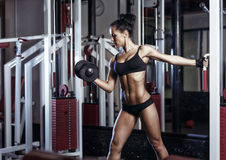 Fitness woman doing exercises with dumbbell in the gym Stock Photos