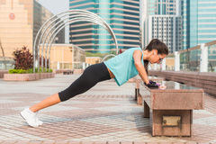 Fitness woman doing feet elevated push-ups on a bench in the city. Sporty girl exercising outdoors Stock Photos