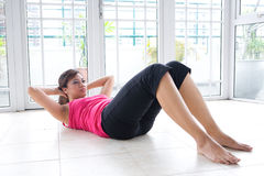 Fitness woman doing her crunching exercise Stock Photos