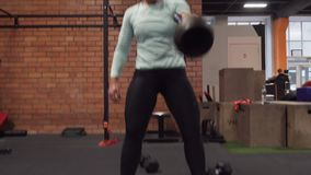 Woman doing kettlebell snatch exercise at fitness gym stock video footage