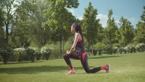 Fitness woman doing lunge exercise on park lawn stock video footage