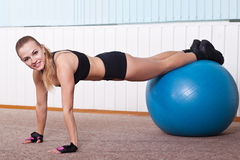 Fitness woman doing push up with ball. In sport hall royalty free stock photo