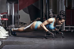 Fitness woman doing push up in the gym. Brunette fitness girl in blue sport wear with perfect body performing push ups stock photography