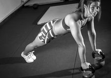 Fitness woman doing push ups with kettlebells royalty free stock photo