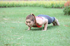 Fitness woman doing push-ups during outdoor cross training worko Stock Photography