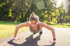 Fitness woman doing push-ups during outdoor cross training workout. Beautiful young and fit fitness sport model training. Outside in park stock images