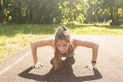 Fitness woman doing push-ups during outdoor cross training workout. Beautiful young and fit fitness sport model training royalty free stock photos