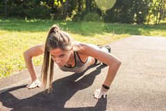 Fitness woman doing push-ups during outdoor cross training workout. Beautiful young and fit fitness sport model training royalty free stock images
