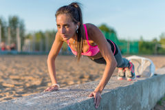 Fitness woman doing push ups Outdoor training workout summer evening. Concept sport healthy lifestyle. Stock Photography