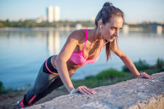 Fitness woman doing push ups Outdoor training workout summer evening side view Concept sport healthy lifestyle. stock image