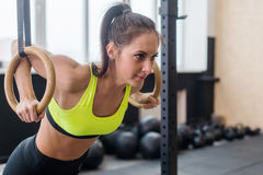 Fitness woman doing push ups training arms with gymnastics rings in the gym Concept workout healthy lifestyle sport. Royalty Free Stock Image