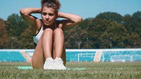 Fitness woman doing sit ups in the stadium working out. Sporty girl exercising abdominal, outdoor One young adult