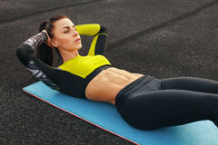 Fitness woman doing sit ups in the stadium working out. Sporty girl exercising abdominals, outdoor.  Royalty Free Stock Image