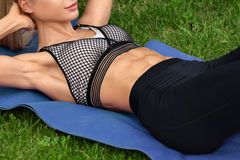 Fitness woman doing sit ups, workout outdoors. Athletic girl exercising abdominal stock image