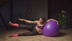 Fitness woman doing stability ball side leg lift