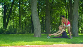Fitness woman doing stretching exercise on green grass at park. Multiracial girlfriends exercising outdoor. Sport woman stretching. Fit girls workout at summer stock footage