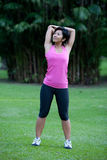 Fitness woman doing stretching exercises. Outdoor in the park stock image