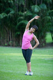 Fitness woman doing stretching exercises. Outdoor in the park stock photography