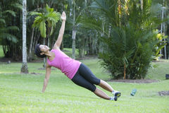 Fitness woman doing stretching exercises. Outdoor in the park royalty free stock photos
